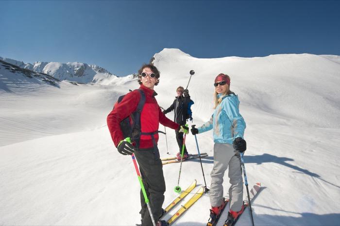 Zauchensee, drei Personen Langlauf in Bergen, Mann zeigen mit Skistock , Portrait